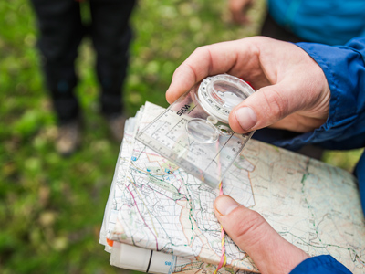 man reading map and using compass