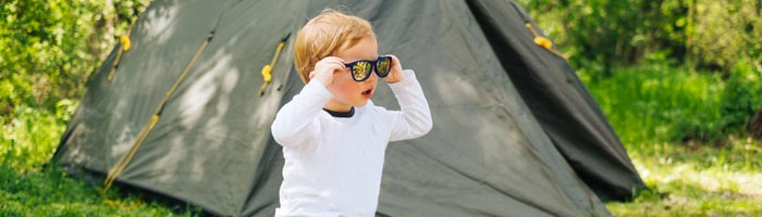 boy wearing sunglasses sitting by tent (shutterstock, Youproduction)