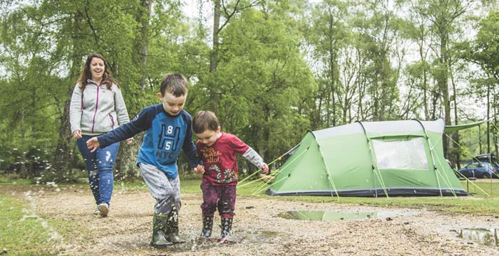 kids-jumping-in-puddle-on-hollands-wood-campsite
