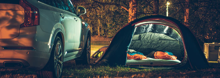 Car next to tent with sleeping bags inside (Shutterstock, welcomia)