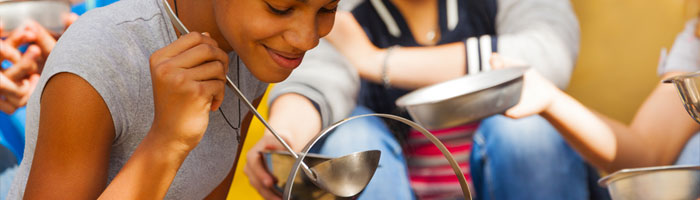 Girl-serving-soup-to-campers (Shutterstock, Sergey Novikov)