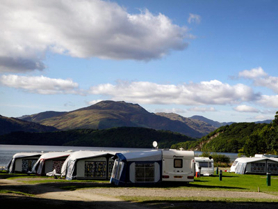 caravans with awnings on one of our Scottish campsites with mountains in the background