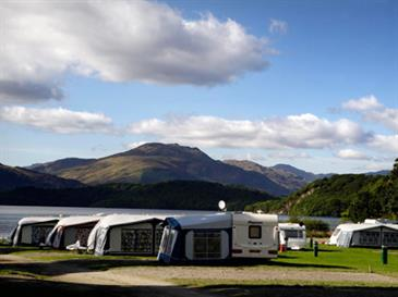 caravans and tents by Loch Lomond with mountains in the background