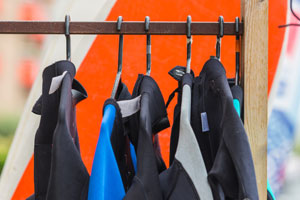 wetsuits on rail for hire (shutterstock, dvoevnore)